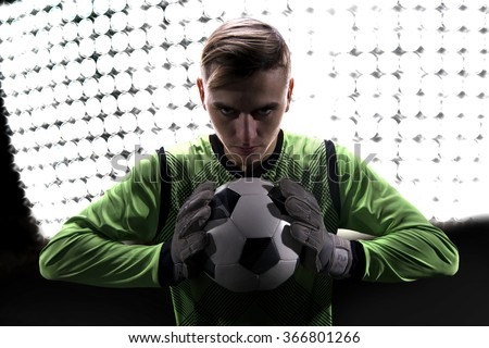 Goalkeeper in green ready to save on highlights - stock photo