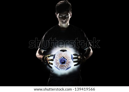 Goalkeeper standing with glowing ball - stock photo