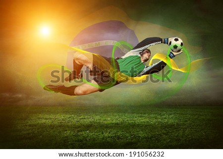 Goalkeeper with ball in action outdoors on the Brasil flag and sunset background - stock photo