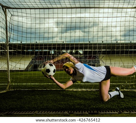 goalkeeper woman stand and jump against goal with net and stadium. female soccer player diving to catch the ball. sporty girl - stock photo