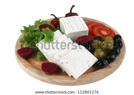 goat cheese served with vegetables on wooden plate - stock photo