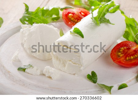 Goat cheese with fresh salad and tomatoes on a white wooden table. Selective focus - stock photo
