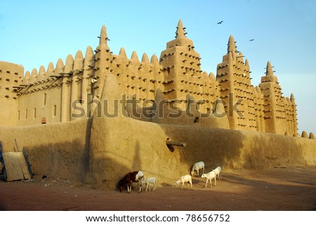 Goats and sheep walking past the Djenne mud mosque in Mali - stock photo