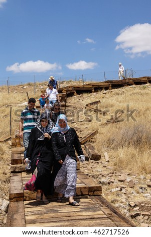GOBEKLI TEPE, TURKEY - JUN 8, 2014 - Tourists descend from visiting the archaeological site