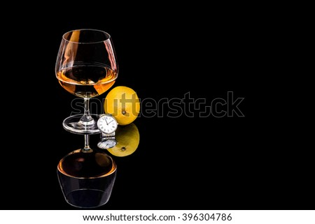 Goblet of Brandy and wrist  watch with lemon on the black background - stock photo