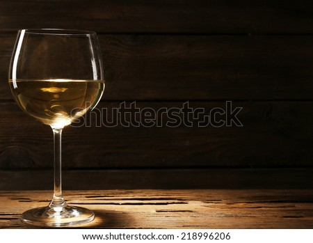 Goblet of white wine on wooden table on wooden wall background - stock photo