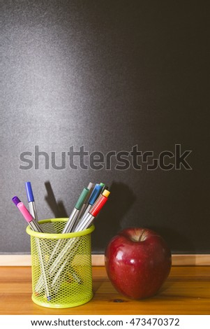 goblet with pen and apple on slate background