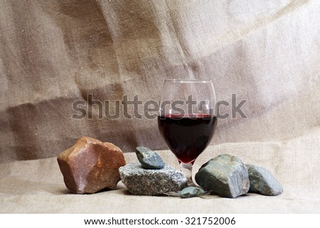 Goblet with red wine near stones on canvas background - stock photo