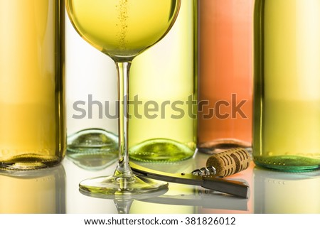 goblet with sparkling white wine and corkscrew with bottles on background - stock photo