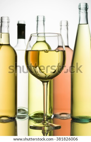 goblet with white wine and bottles on background - stock photo
