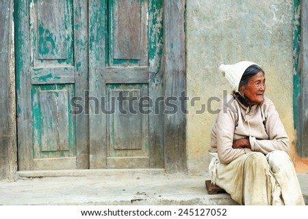 GODAWARI, NEPAL - OCTOBER 15: Old nepalese woman sits on the floor before the paint faded green door of her house in a street of Godawari on October 15, 2012. Lalitpur distr.-Bagmati zone-Nepal.