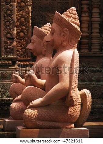 Gods sculptures at Banteay Srei, the temple of women, near Angkor Wat (Siem Reap, Cambodia). - stock photo