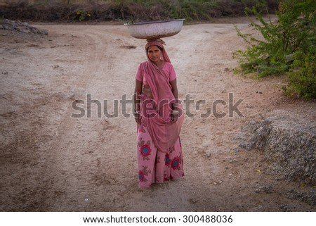 GODWAR REGION, INDIA - 14 FEBRUARY 2015: Indian woman in pink sari stands alone in dirt track with metal container balanced on head. - stock photo