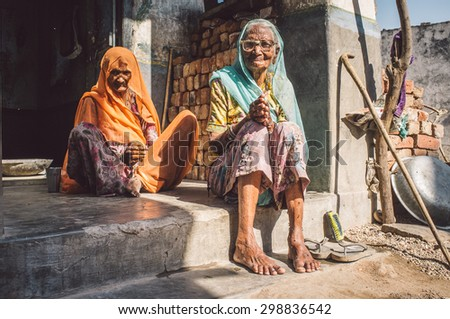 GODWAR REGION, INDIA - 13 FEBRUARY 2015: Two elderly Indian woman in sari's with covered heads sit in doorway of home. Post-processed with grain, texture and colour effect. - stock photo