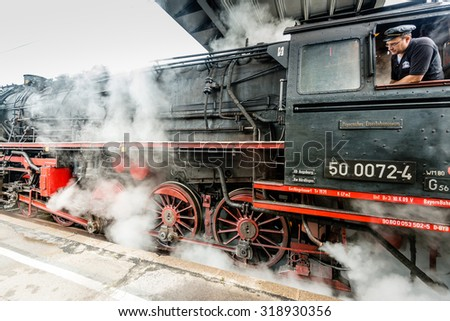 GOEPPINGEN, GERMANY - SEPTEMBER 19, 2015: A train driver is starting the engines of an old steam locomotive in the station of Goeppingen, Germany during the Maerklin Days 2015: Maerklin, the largest - stock photo