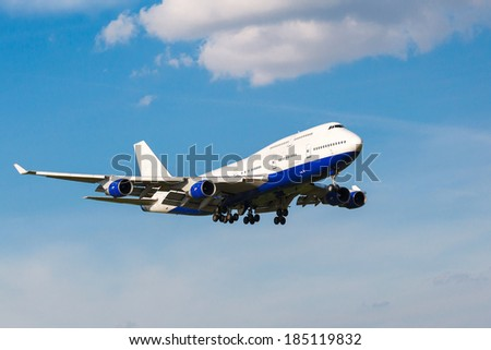 going to land a white passenger jet with landing gear on the background of blue sky, view from below