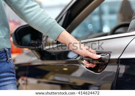 Going to test it. Low angle cropped closeup of a female buying a car holding her hand on the door handle - stock photo