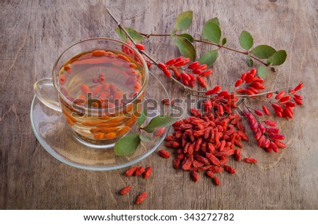 goji fresh antioxidant tea in glass cup and barberries in wooden desk