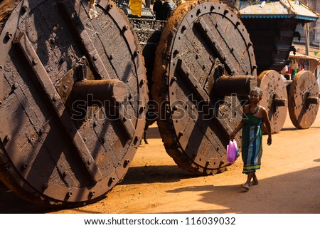 GOKARNA, INDIA - MARCH 3: Unidentified Indian woman walks by enormous wooden wheels of the big ratha chariot, a vehicle used in Gokarna for hindu festivals, on March 3, 2009 in Gokarna, India - stock photo
