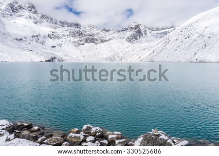 Gokyo lake (Dudh Pokhari) in Everest region, Nepal. View of Renjo Pass covered with snow on the opposite side of the lake. - stock photo