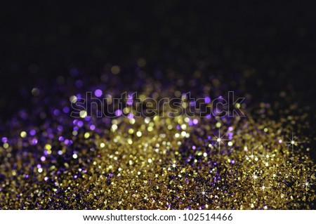 Gold and purple glitter on black background with selective focus - stock photo