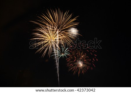 Gold and red fireworks light a black night sky - stock photo