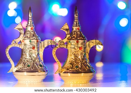 Gold and Silver Arabic Coffee pots in colorful illuminated background. Ramadan and Eid concept - stock photo