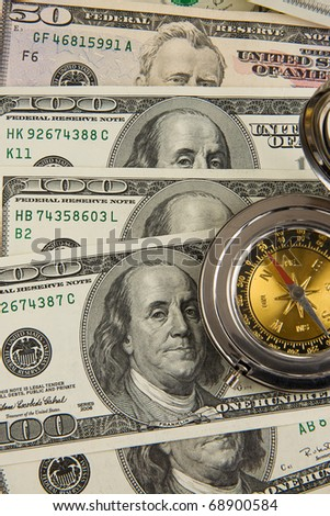 gold and silver compass on dollars