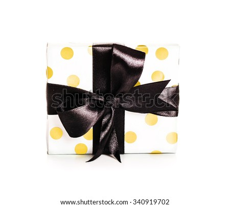 Gold and white polka dotted gift box with black bow - stock photo