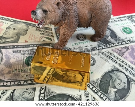 Gold bar, bear and US dollar banknotes on red background  - stock photo