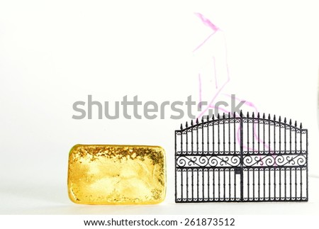 Gold bar beside the plastic gate model in the scene appear the hand drawing house shape on clear acrylic surface represent the mortgage concept idea. - stock photo