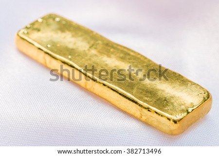 Gold bar, ingot on cloth background. Macro.