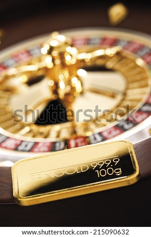 Gold bar on roulette wheel - stock photo