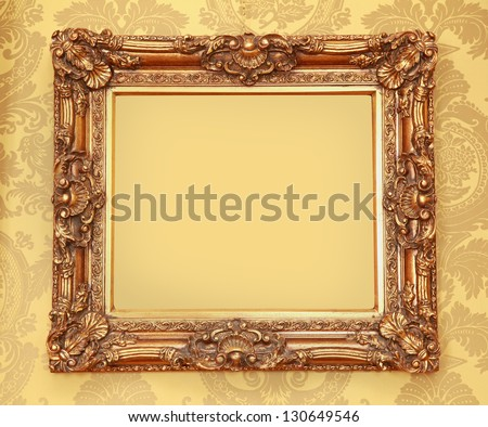 Gold Baroque frame with carved edges on beige wall