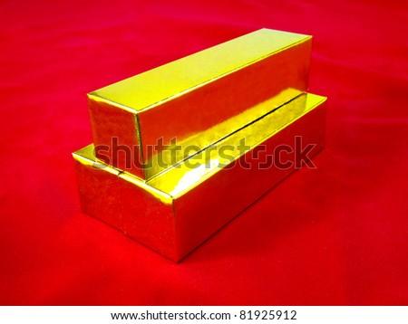 Gold bars on red velvet - stock photo