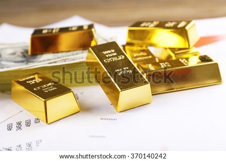 Gold bars with dollar banknotes on paper background, close up - stock photo