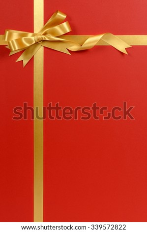 Gold bow and ribbon, red background, copy space, vertical - stock photo