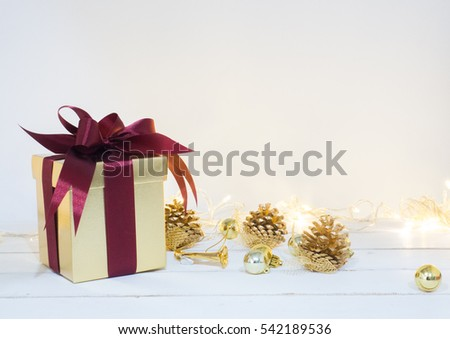 Gold box with red ribbon and decoration golden object white background with small lighting  on wooden table for Christmas and The New Year .