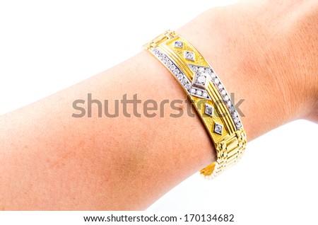 Gold bracelet holding hand on isolated white background - stock photo