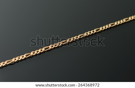 Gold chain lying on black table. - stock photo