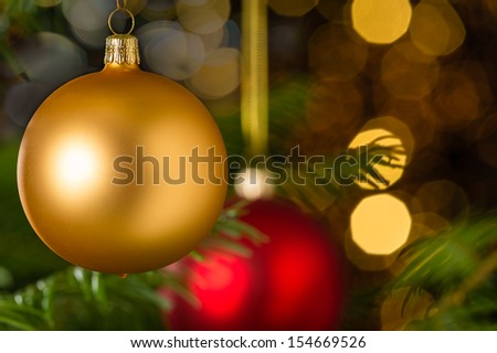 Gold christmas bauble hanging on Xmas tree sparkling lights background - stock photo
