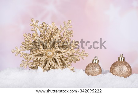 Gold Christmas baubles and star in snow with colorful holiday background - stock photo