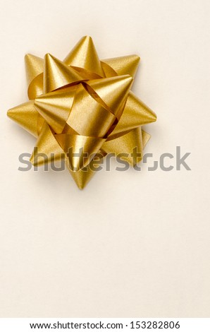 Gold Christmas bow on yellow paper background. - stock photo
