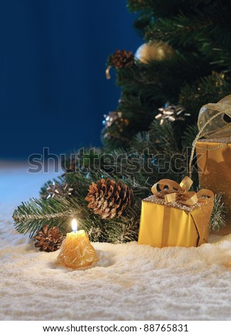 gold Christmas gift boxes with burn candles under decorated fir on snow