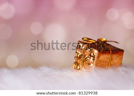 Gold Christmas gift on background of defocused lights. Shallow DOF. - stock photo