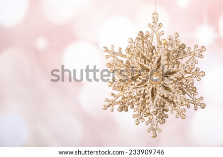 Gold Christmas ornament against a colorful background - stock photo