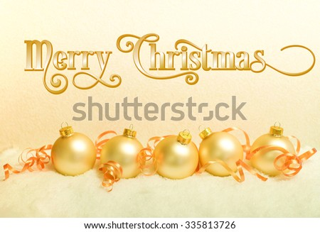 Gold Christmas ornaments on snow with curled ribbon accents and the message Merry Christmas in fancy text - stock photo