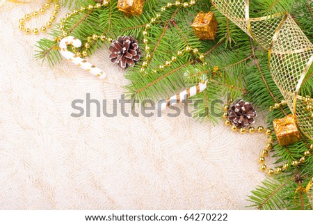 Gold Christmas ribbon, balls and beads on green pine branch