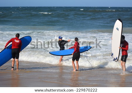 GOLD COAST, AUS - NOV 01 2014:Female wave surfing instructor teaches men and women how to surf in Surfers Paradise, Queensland, Australia. - stock photo