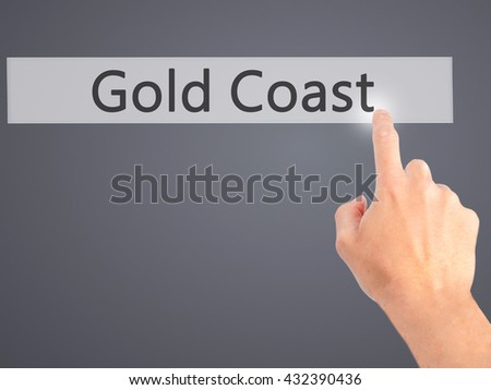 Gold Coast - Hand pressing a button on blurred background concept . Business, technology, internet concept. Stock Photo